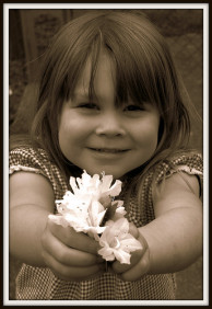 Little girl holding out flower