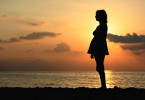 silhouette of pregnant woman in sunset