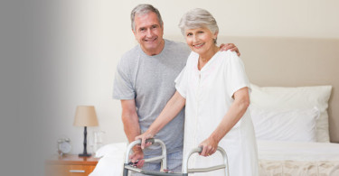 Elderly couple standing in bedroom with walker