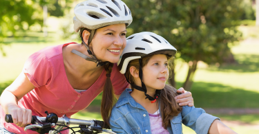 mom and daughter riding bikes in helmets