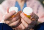 Elderly holding medication bottles