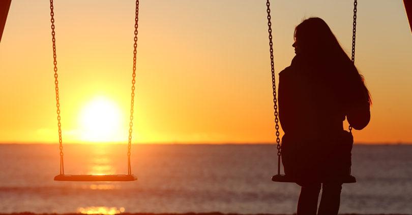 sihouette of woman on swingset