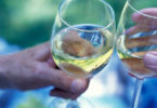 hands toasting wine glasses