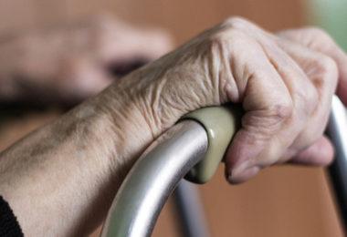 Elderly hands and a walker