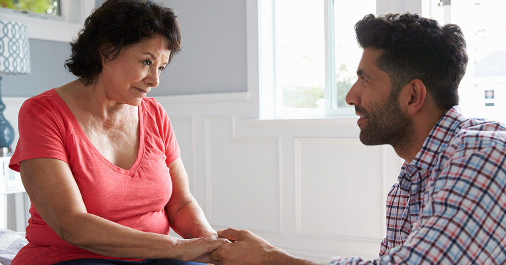 Son talking to elderly mother with Alzheimer's