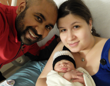 Anna Sophia and her husband pose with their first-born child