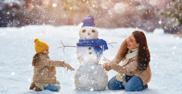 mom and child building a snowman