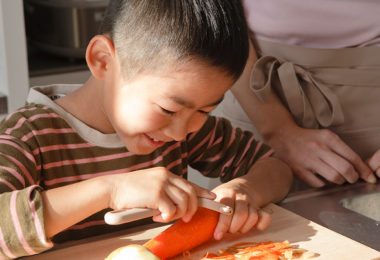 little boy peeling a carrot