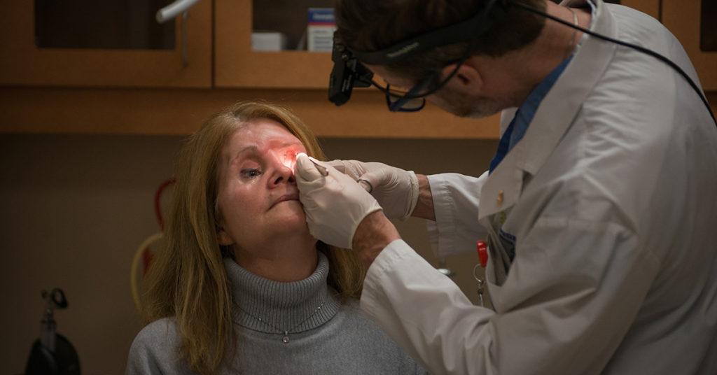 Dr. Kevin Higgins examines Brenda Coulter several weeks after surgery.