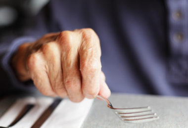 Elderly person eating pizza