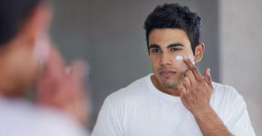 man applying moisturizer to face