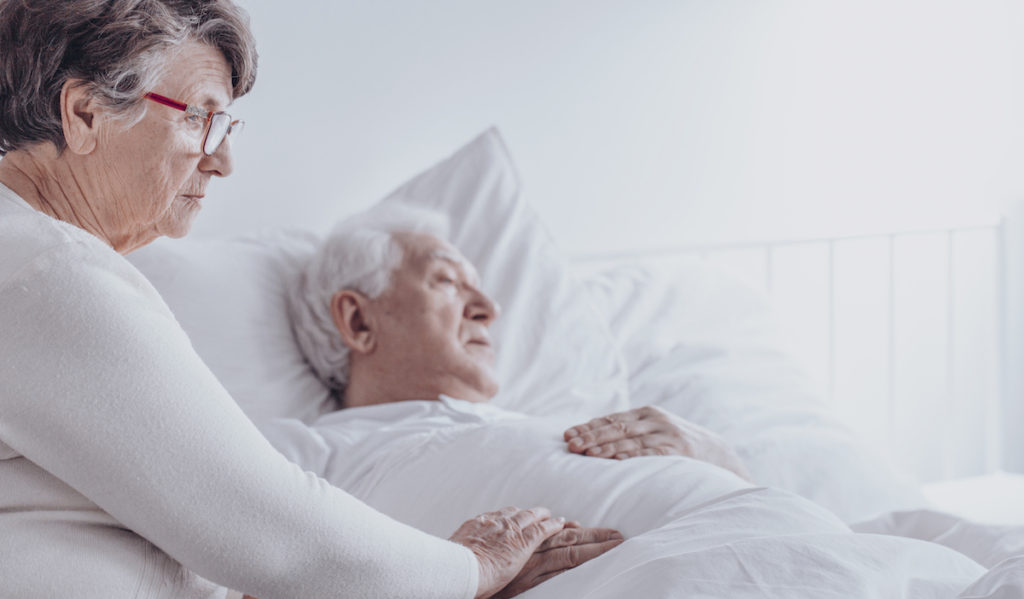 Elderly woman supporting sick husband