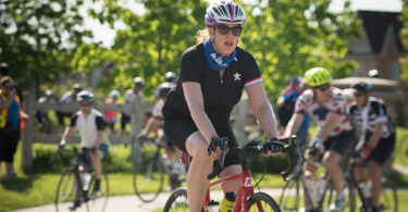 A woman wearing sunglasses and a bicycle helmet cycles towards the right-hand side of the image.