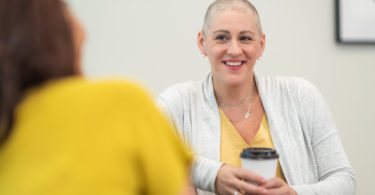 woman with breast cancer talking with research assistant
