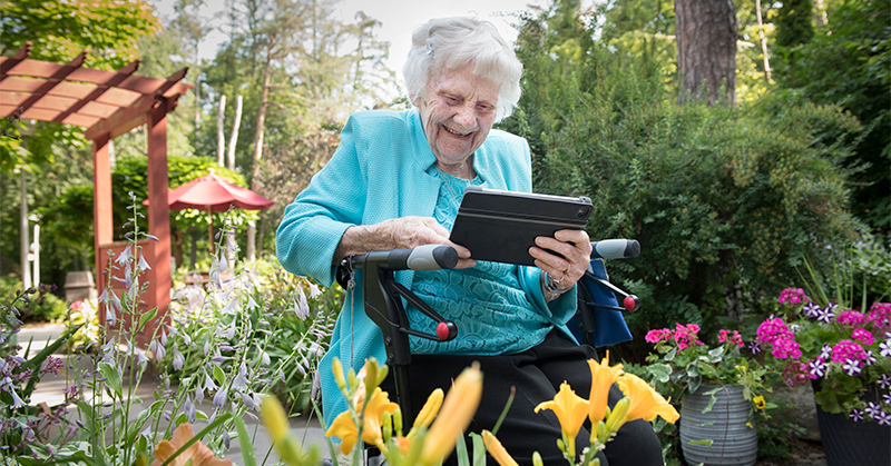 A senior woman smiles as she takes a photograph of a yellow flower.