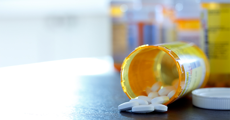 A half-full pill bottle lays on its side on a table, with a few pills spilling out.