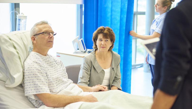 man in hospital bed with wife nearby