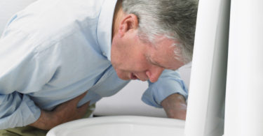 man leaning over toilet