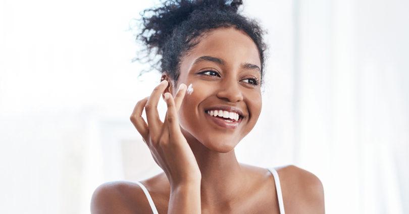 woman moisturizes face