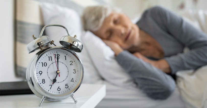 A woman sleeps behind a clock that strikes 7:00 a.m.