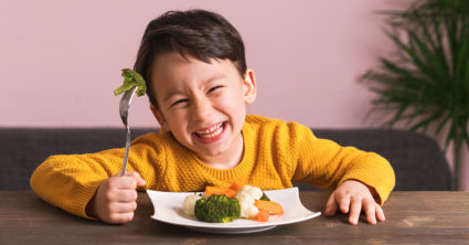 A child smiles as he lifts a piece of broccoli up with his fork.