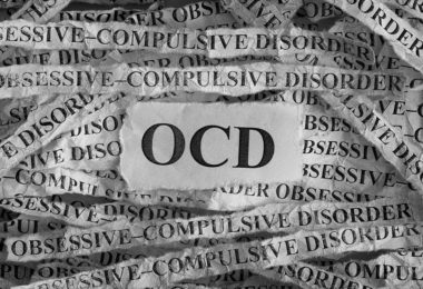 """Strips of the word """"obsessive-compulsive disorder"""" are laid behind the acronym OCD."""