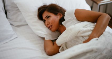 woman awake with cramps