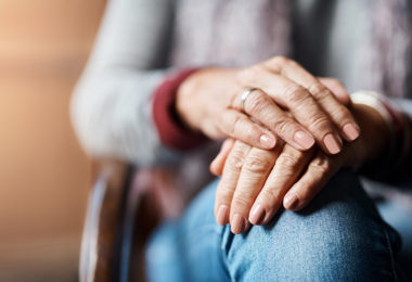 Senior woman sitting on a chair with her hands on her knee.