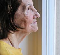 Elderly woman gazing out window