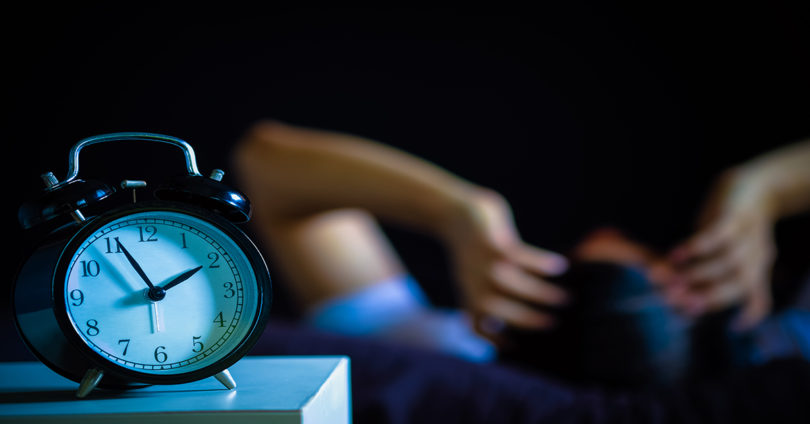 A man lays sleepless behind a clock that is nearing 2 a.m.