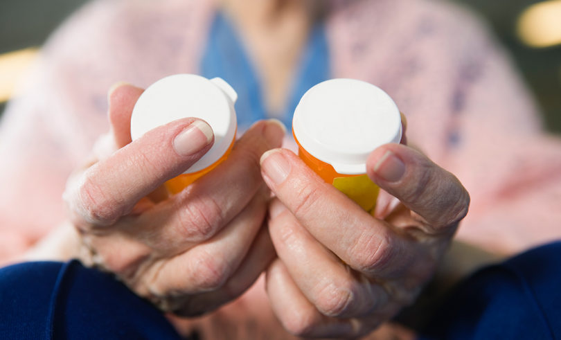 Elderly holding medication bottles