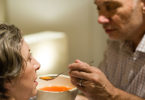 Man feeds soup to his wife, helping her to eat