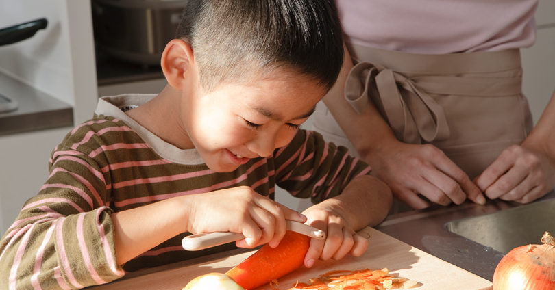 little boy peeling a carrot