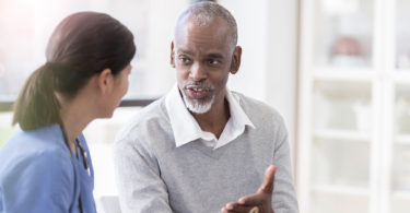 Man speaking with a health-care provider