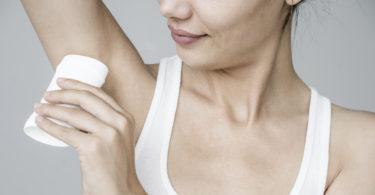 Woman applying deodorant on her armpit