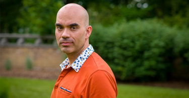 A man wearing an orange shirt peers over his left shoulder. He is standing infront of green bushes, which are blurred in the background.