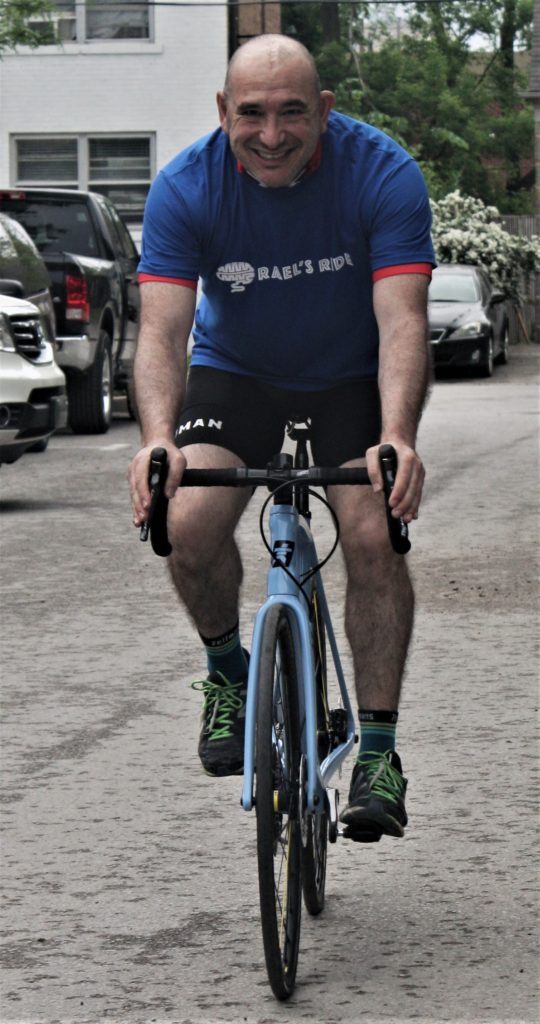 A man wearing a blue t-shift smiles as he rides a bicycle.