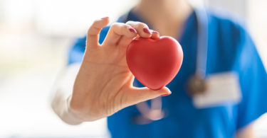 A nurse holds up a heart in her hand.