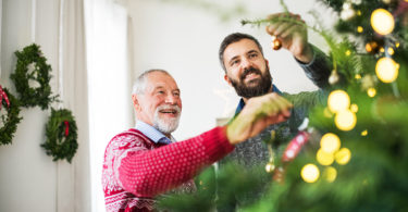 Adult son and father decorate Christmas tree