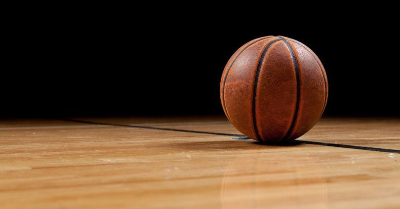 A single basketball sits on a basketball court.