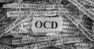 "Strips of the word ""obsessive-compulsive disorder"" are laid behind the acronym OCD."