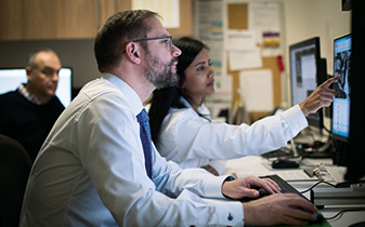 Radiation oncologist Dr. Danny Vesprini and radiation therapist Susana Sabaratram look at a monitor.