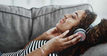 Listening to music through headphones.