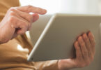 An elderly woman uses a tablet.