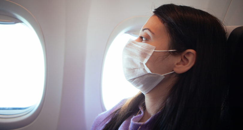 woman on airplane wearing a mask
