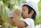 A baby drinks from a water bottle.