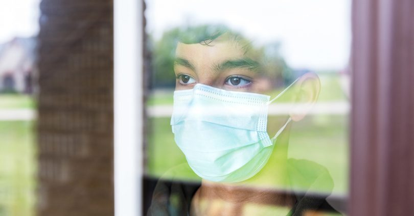 A child wearing a face mask peers out a window.