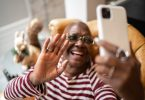 Senior woman waving during a video call on smartphone