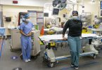 Nurses Natacha and Shauna pose next to a stretcher in Sunnybrook's emergency department
