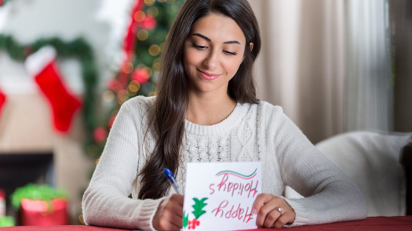 A young woman at home, surrounded by Christmas decorations, writing in a card that reads 'happy holidays'